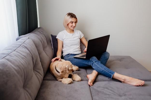 Jeune femme blonde avec un épagneul assis à un blogueur portable travaillant sur internet home office