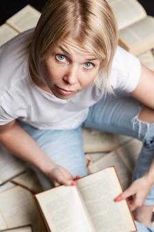 Jeune femme blonde est assise sur une pile de livres et lit. éducation, connaissances et loisirs. verticale.