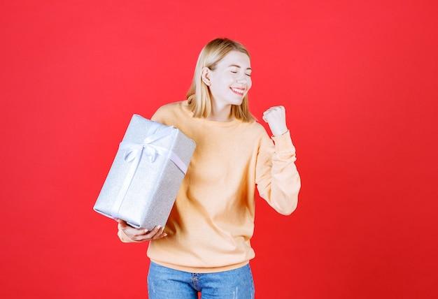 Jeune femme blonde est heureuse de son succès tout en tenant la boîte-cadeau grise devant le mur rouge