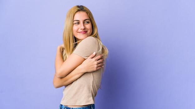 Jeune femme blonde étreint, souriant insouciant et heureux.