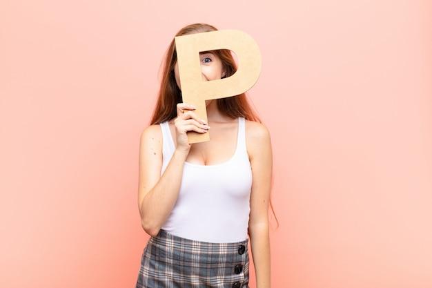 Jeune femme blonde excitée, heureuse, joyeuse, tenant la lettre p de l'alphabet pour former un mot ou une phrase.