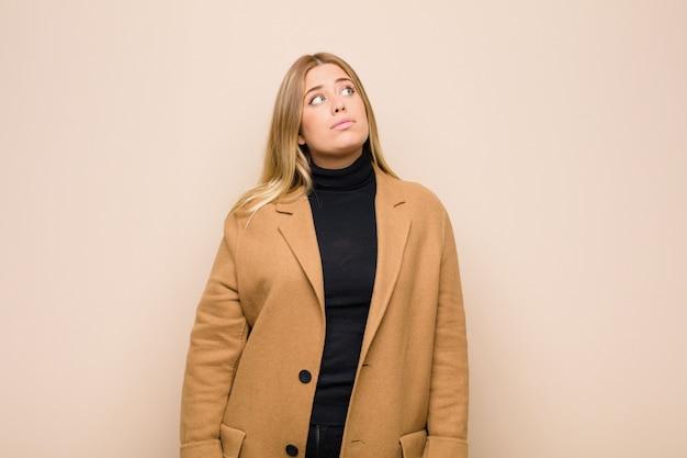 Jeune femme blonde avec une expression inquiète, confuse et désemparée, levant les yeux, doutant du mur