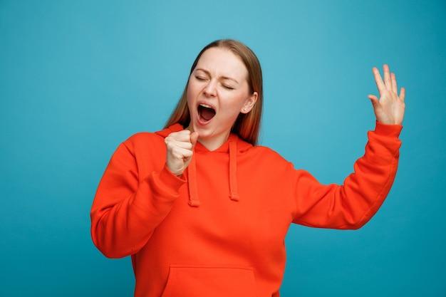 Jeune femme blonde faire semblant de tenir le microphone levant la main en chantant avec les yeux fermés