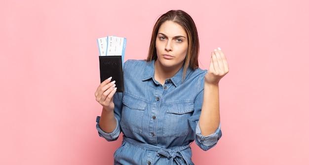 Jeune femme blonde faisant capice ou geste d'argent, vous disant de payer vos dettes!
