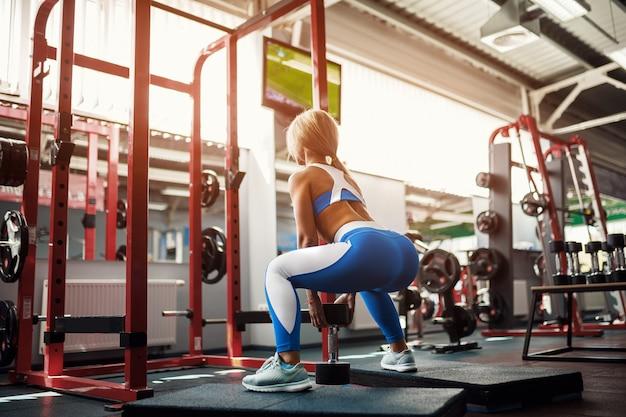 Jeune femme blonde faisant du squat
