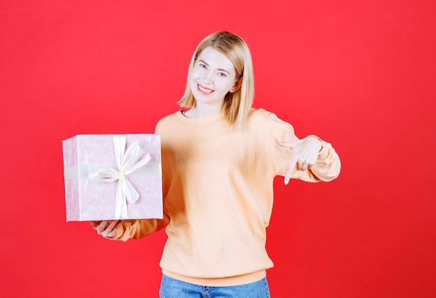 Jeune femme blonde fait un signe vers le bas tout en tenant la boîte-cadeau devant le mur rouge