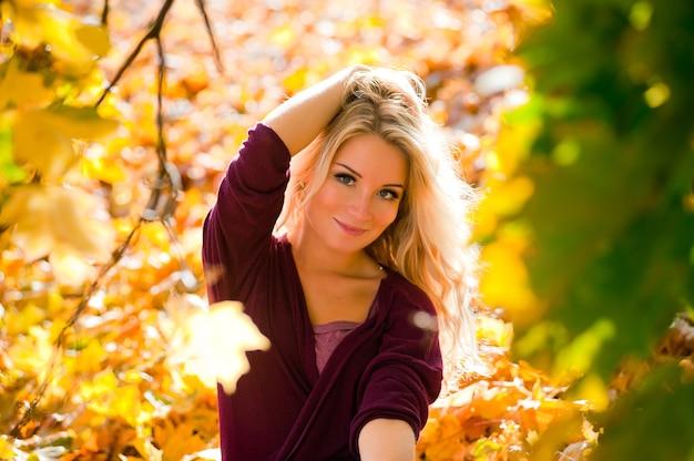 Jeune femme blonde avec des feuilles d'automne à la main et jaune d'automne
