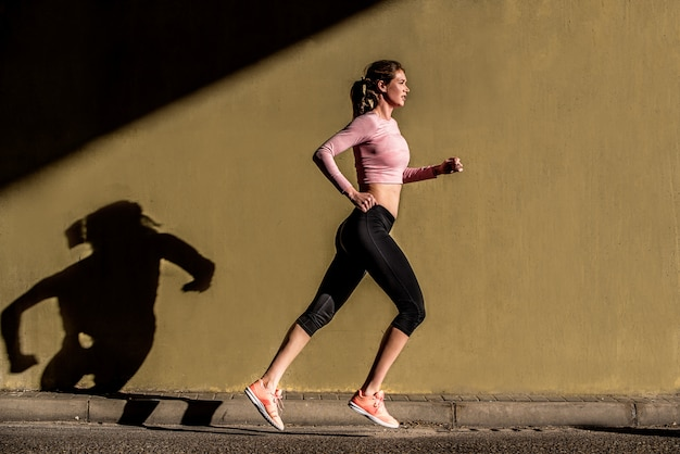 Jeune femme blonde fit courir dans la rue