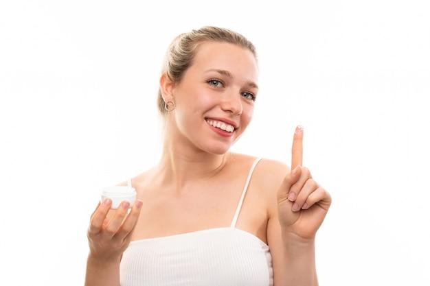 Jeune femme blonde sur fond blanc isolé avec une crème hydratante