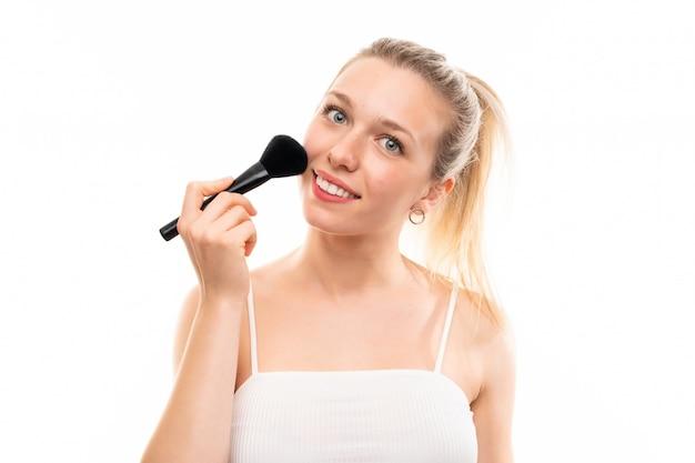 Jeune femme blonde sur fond blanc isolé avec un pinceau de maquillage