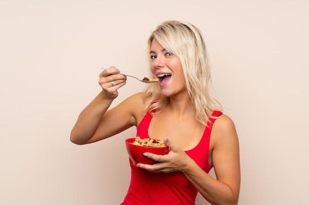 Jeune femme blonde sur fond isolé tenant un bol de céréales