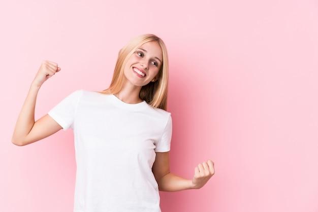 Jeune femme blonde sur fond rose levant le poing après une victoire, concept gagnant.