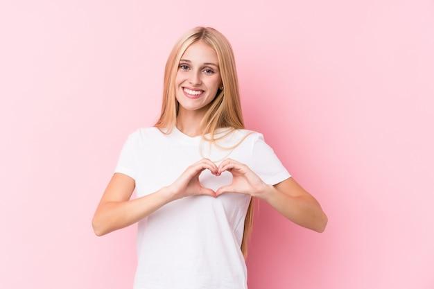 Jeune femme blonde sur fond rose souriant et montrant une forme de coeur avec les mains.