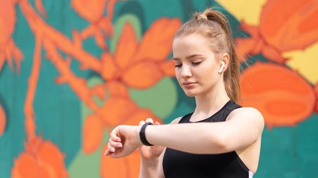 Jeune femme blonde à la formation en plein air dans les vêtements de sport est sur son bracelet de remise en forme, fond multicolore