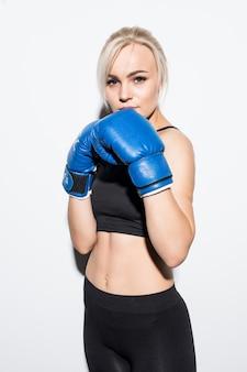 Jeune femme blonde avec des gants de boxe bleus prêts à se battre sur blanc