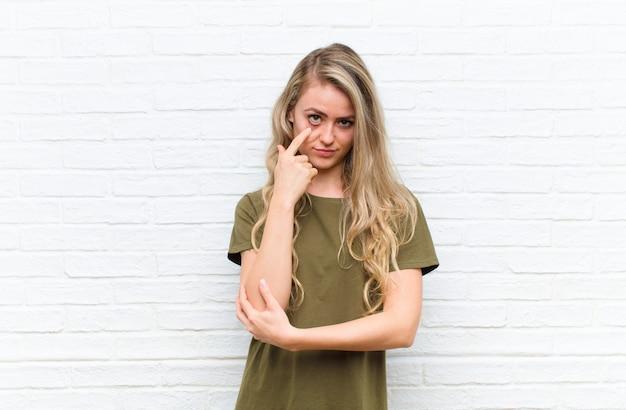Jeune femme blonde en gardant un œil sur vous, ne pas faire confiance, regarder et rester vigilant et vigilant sur fond de mur de briques