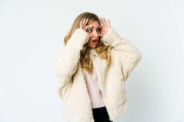 Jeune femme blonde en gardant les yeux ouverts pour trouver une opportunité de succès