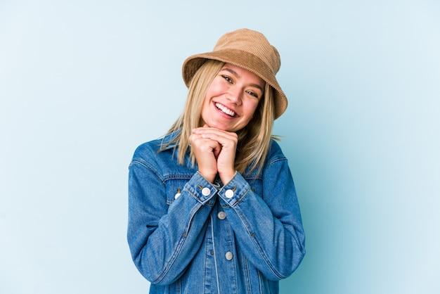 Jeune femme blonde garde les mains sous le menton, regarde joyeusement de côté