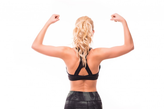 Jeune femme blonde en haut noir montre ses muscles du dos isolé sur blanc