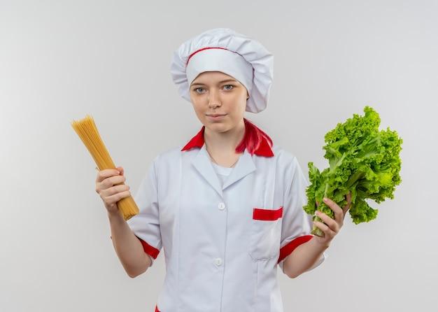 Jeune femme blonde heureuse chef en uniforme de chef détient bouquet de spaghettis et salade isolé sur mur blanc