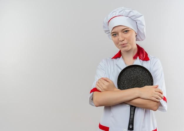 Jeune femme blonde heureuse chef en uniforme de chef détient une poêle à frire avec bras isolé sur mur blanc