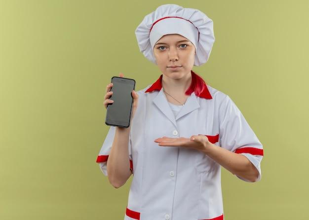 Jeune femme blonde heureuse chef en uniforme de chef tient et pointe avec la main au téléphone isolé sur mur vert