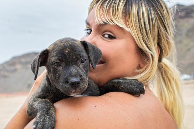 Jeune femme blonde, heureuse avec son chien chiot pris dans ses bras.