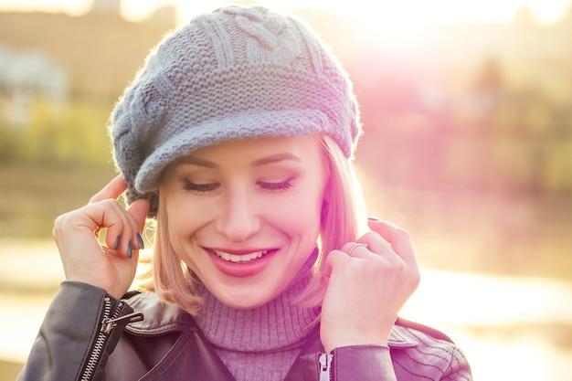 Jeune femme blonde heureuse souriante au regard naïf en manteau de béret bleu français et chapeau chaud en plein air portrait agrandi peau parfaite et maquillage de jour dans le parc en automne. froid dehors. vêtements de printemps d'hiver