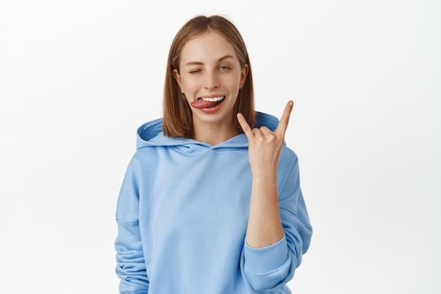 Jeune femme blonde impertinente et heureuse appréciant la fête, s'amusant, montrant la langue, clignant de l'œil avec du heavy metal, rock sur le geste des cornes, debout dans un sweat à capuche bleu contre un mur blanc.