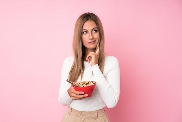 Jeune femme blonde sur isolé tenant un bol de céréales et de penser