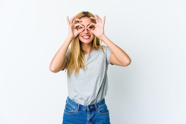 Jeune femme blonde isolée sur blanc excité en gardant le geste ok sur les yeux.