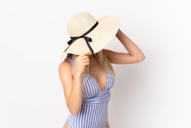 Jeune femme blonde isolée sur blanc en maillot de bain en vacances d'été