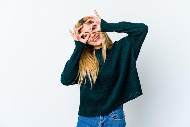 Jeune femme blonde isolée sur blanc montrant un signe correct sur les yeux