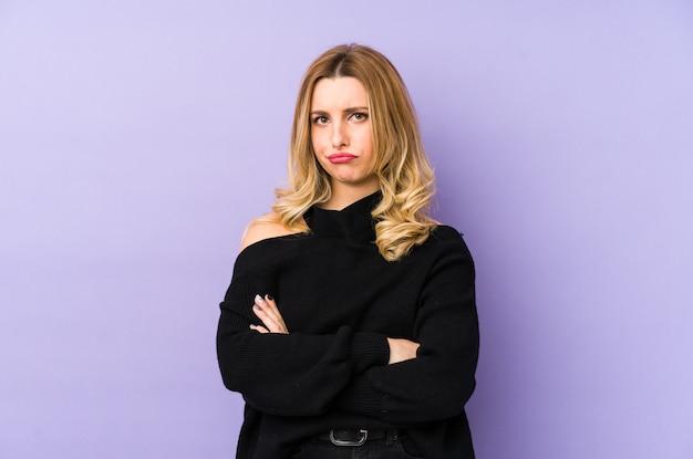 Jeune femme blonde isolée face à froncer les sourcils de mécontentement, garde les bras croisés.