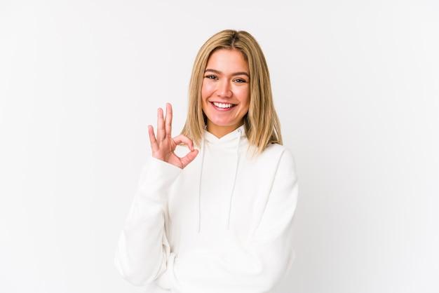 Jeune femme blonde isolée fait un clin d'œil et détient un geste correct avec la main