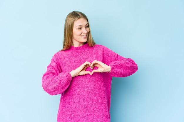 Jeune femme blonde isolée sur fond bleu souriant et montrant une forme de coeur avec les mains.