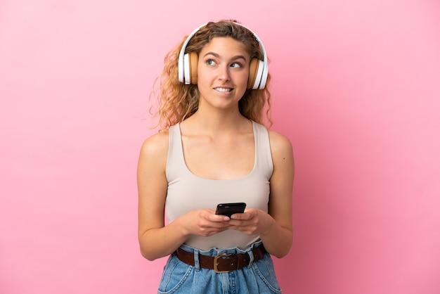 Jeune femme blonde isolée sur fond rose écoutant de la musique avec un mobile et pensant