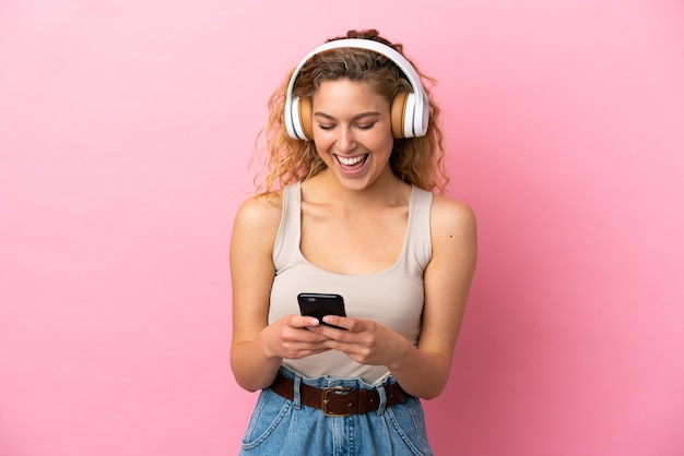 Jeune femme blonde isolée sur fond rose écoutant de la musique et regardant vers un mobile