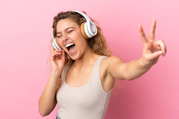 Jeune femme blonde isolée sur fond rose, écouter de la musique et chanter