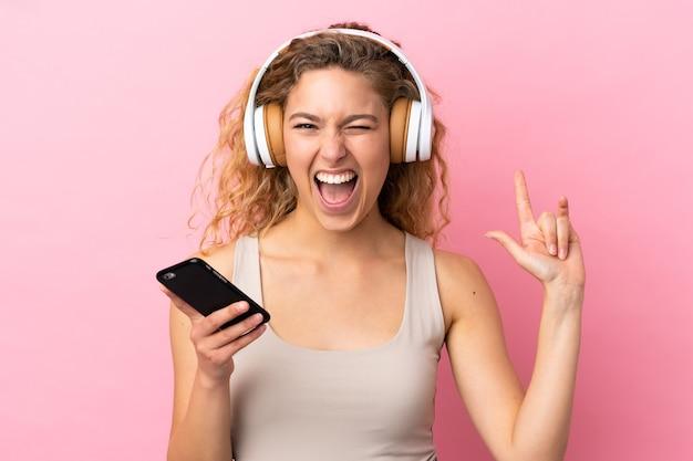 Jeune femme blonde isolée sur fond rose, écouter de la musique avec un mobile faisant un geste rock