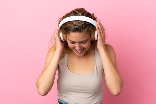 Jeune femme blonde isolée sur fond rose, écouter de la musique