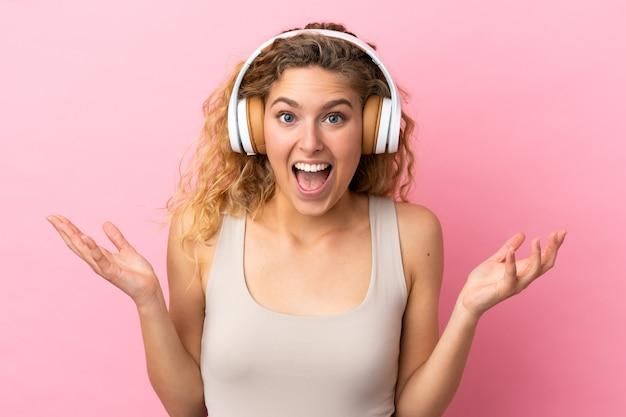 Jeune femme blonde isolée sur fond rose surpris et écoutant de la musique
