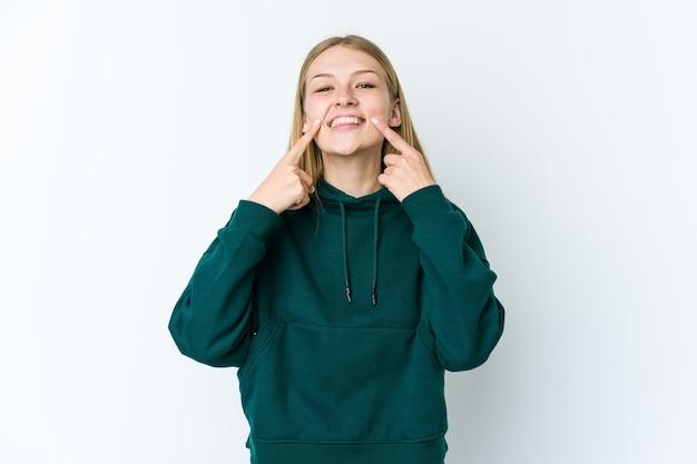 Jeune femme blonde isolée sur le mur blanc sourit, pointant du doigt la bouche.