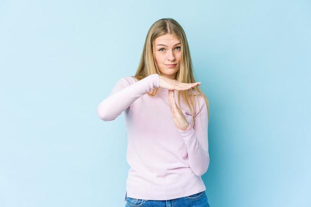 Jeune femme blonde isolée sur un mur bleu montrant un geste de temporisation.