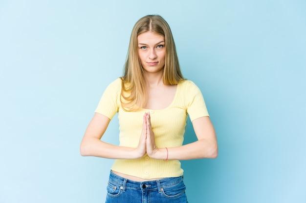 Jeune femme blonde isolée sur le mur bleu priant, montrant la dévotion, personne religieuse à la recherche d'inspiration divine