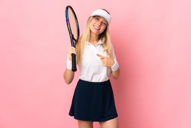 Jeune femme blonde isolée sur un mur rose jouant au tennis et pointant vers le côté