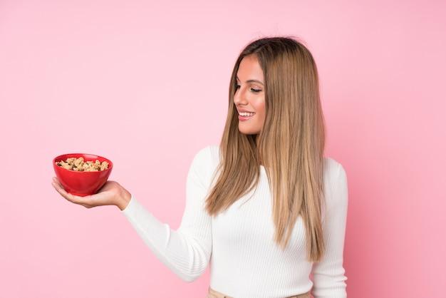 Jeune femme blonde isolée rose tenant un bol de céréales
