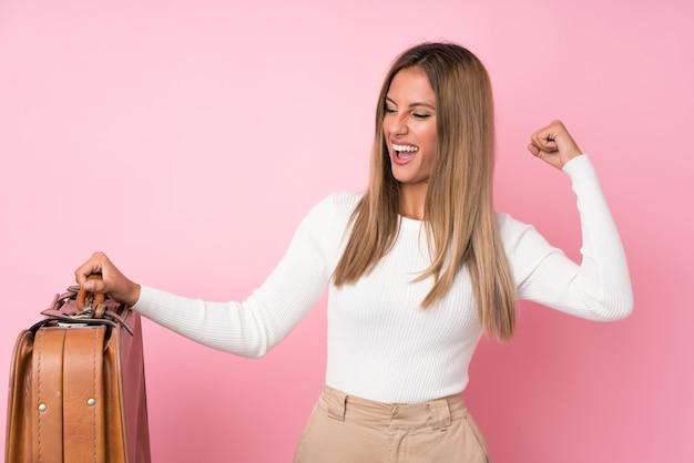 Jeune femme blonde isolée rose tenant une mallette vintage
