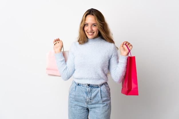 Jeune femme blonde isolée tenant des sacs à provisions et souriant