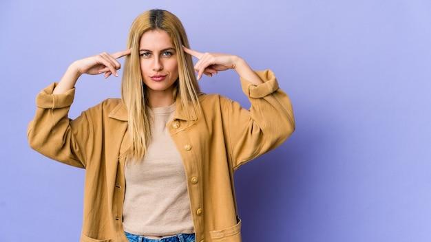 Jeune femme blonde isolée sur violet concentré sur une tâche, gardant l'index pointant la tête.